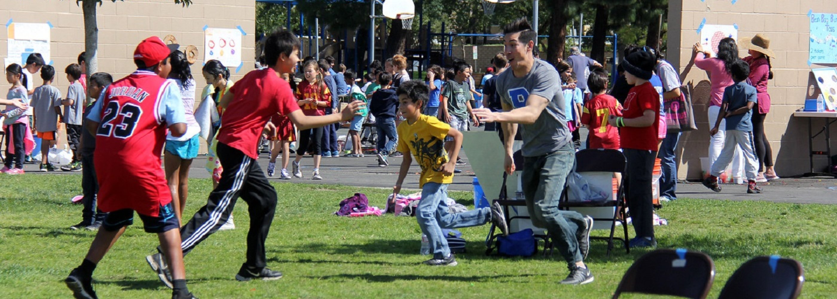 Teacher and Students Playing in Field
